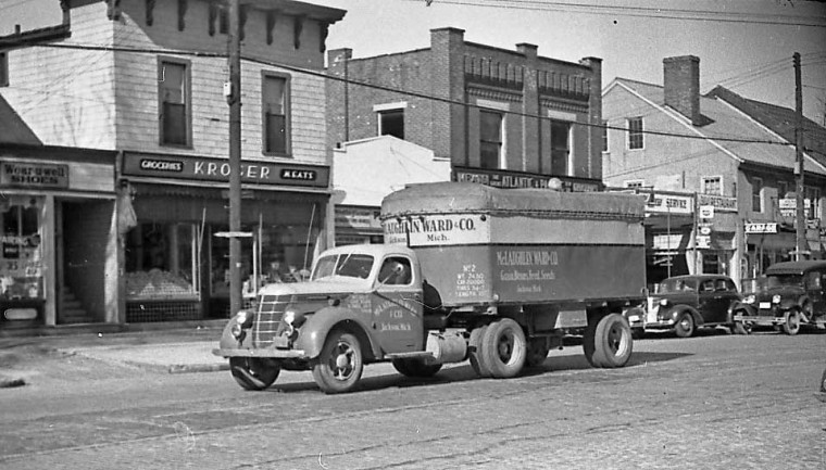 """1937 or later International Tractor and trailer, a Chevrolet, and a Model """"A"""" Ford Sedan Delivery"""